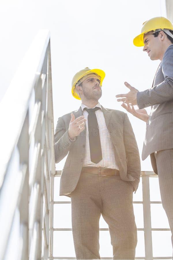 Sikt för låg vinkel av unga manliga affärsmän i hårda hattar som har diskussion på trappan mot klar himmel royaltyfri fotografi