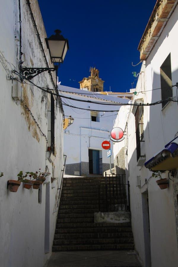 Sikt för låg vinkel på den smala tomma gränden med fasader av vita hus och moment som kontrasterar uppför trappan med mörkt - blå royaltyfri fotografi