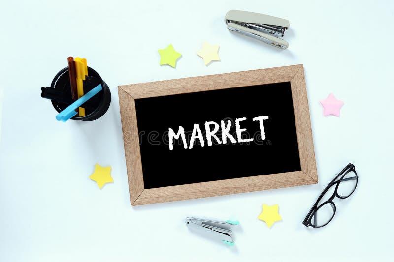 Sikt f?r marknadsord ?verst av svart tavla med exponeringsglas, pennfallet, h?ftapparater och mark?ren royaltyfria foton