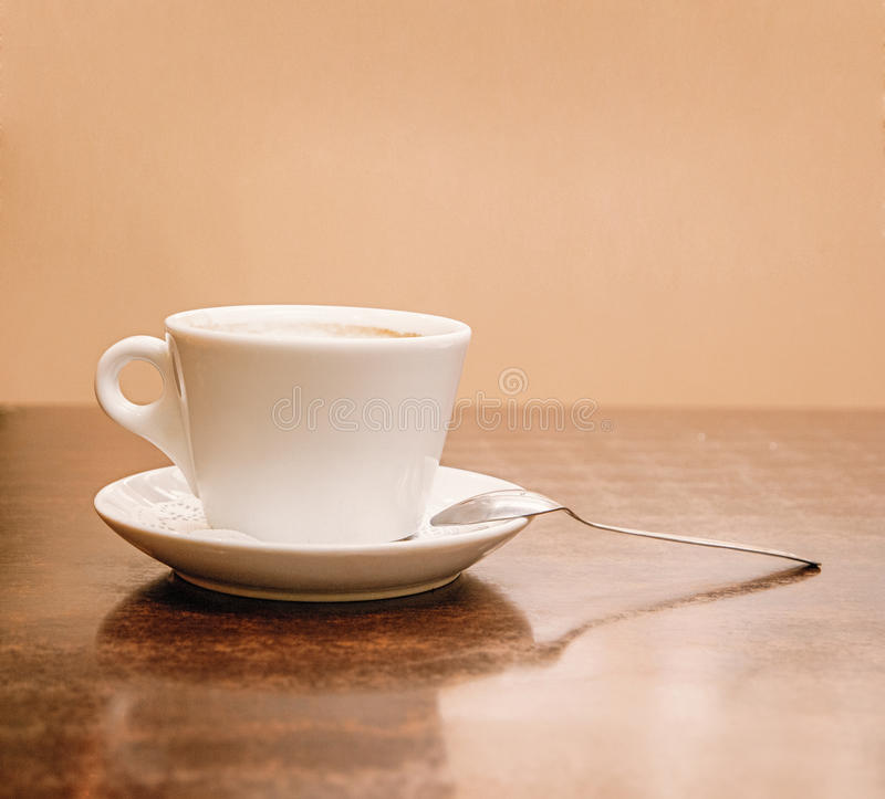 Sikt för sida för kaffekopp på trätabellen Mycket utrymme för text på väggen på bakgrund arkivfoto