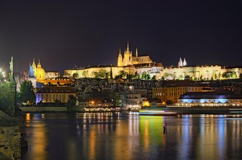 Sikt för sommarnatt av gamla Prague Vltava flod, Charles Bridge med belysning och Prague slott med St Vitus Cathedral royaltyfria foton