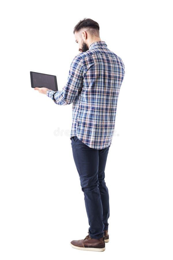 Sikt för tillbaka sida av den unga affärsmannen som använder och arbetar på minnestavladatoren arkivbild