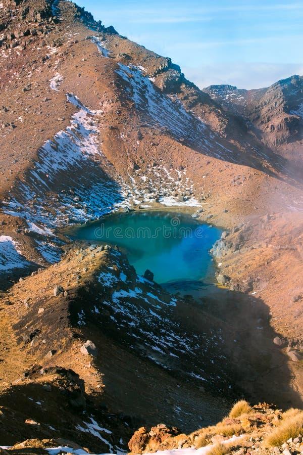 Sikt för turkossmaragdsjö och aktiv vulkan som röker sulphur från overklig vulkanisk terräng, Tongariro nationalpark royaltyfri fotografi