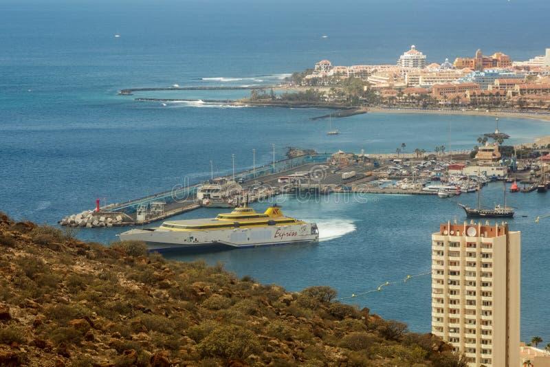 Sikt f?r Los Cristianos fr?n det Guaza berget Färja till La Gomera som lämnar portfjärden kanarief?gel?ar tenerife spain fotografering för bildbyråer