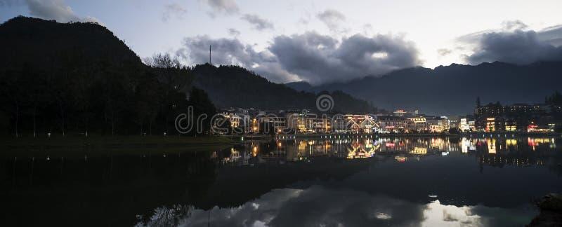 Sikt f?r nattstadslandskap med bergbakgrund och reflexion f?r molnig himmel p? vatten som lokaliseras p? SAPA, Vietnam royaltyfria bilder