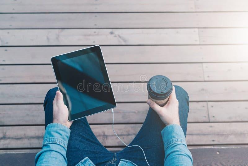 Sikt från ögon Närbild av den digitala minnestavlan med den tomma skärmen och koppen kaffe i händer av hipstermannen royaltyfria bilder