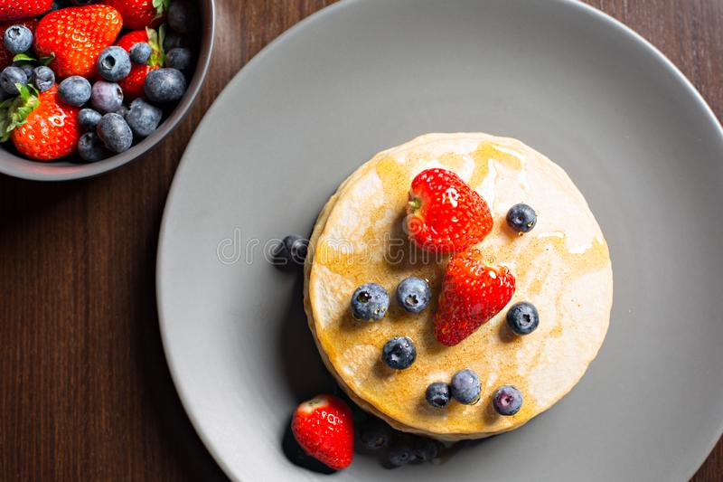 Sikt från över av klassiska amerikanska pannkakor, med jordgubbar och nya blåbär arkivfoton