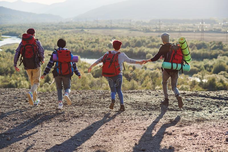 Sikt från baksida av fyra hipstervänner med loppryggsäcken som rymmer händer och framåtriktat kör till berget på solnedgång arkivbilder