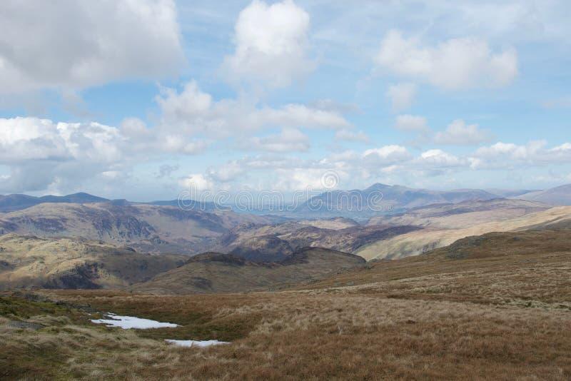 Sikt från berget i sjöområdet Cumbria, UK: sjöar och berg, blå himmel och moln arkivbilder