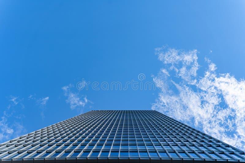 Sikt från botten av kontorstornskycrapper som bygger med exponeringsglasfönster i blå himmel för moln arkivfoton
