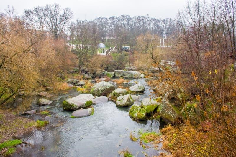 Sikt från bron på en liten flod som flöden till och med stenblocken och granitstenkanjonen i bakgrunden på kullarna fotografering för bildbyråer
