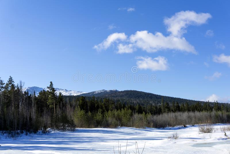Sikt från dalen av en djupfryst flod till bergskedjan av de nordliga Uralsna i en solig dag för vinter arkivfoton