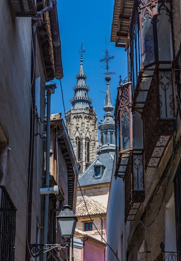 Sikt från de forntida gatorna av tornspiran av Toledo Cathedral och Iglesiaen de arkivfoton