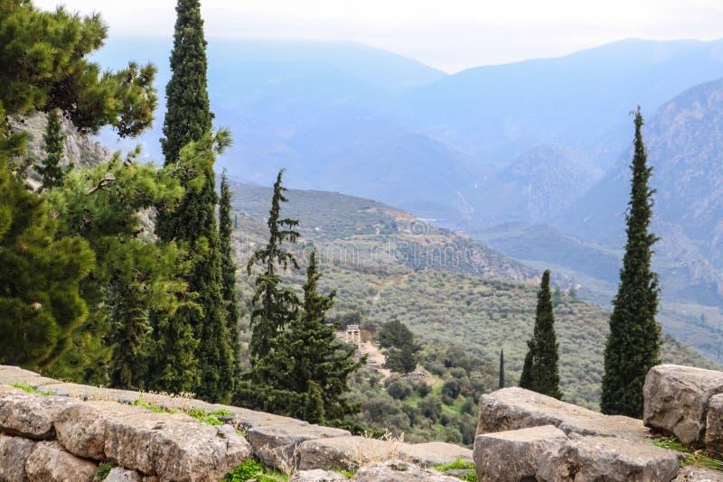 Sikt från den arkeologiska platsen för bergssida av forntida Delphi Greece som ser ner in i dalen och på templet av Athena under arkivbilder