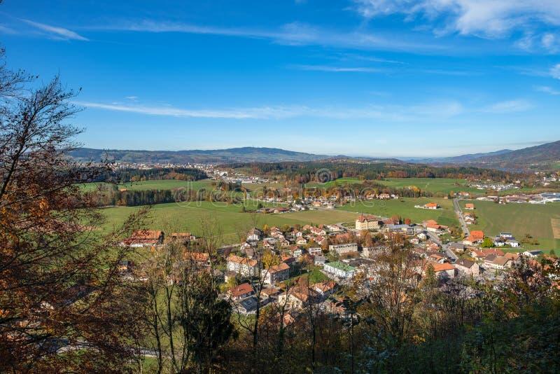 Sikt från den Gruyeres slottkullen, Schweiz på den Gruyeres byn och de omgeende fjällängarna royaltyfri foto