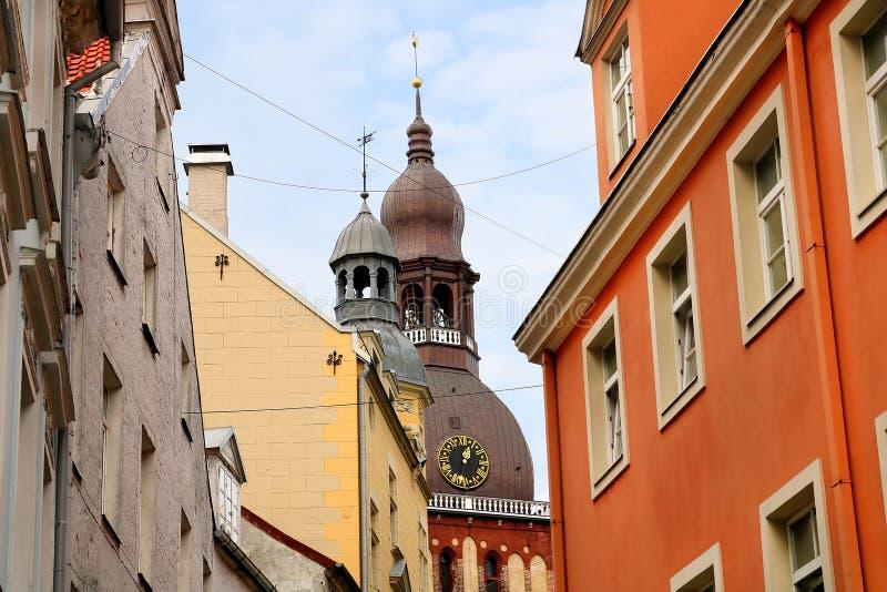 Sikt från den Kramu gatan till de gamla byggnaderna och bästa sikt av den Riga domkyrkan, gammal stad, Riga arkivfoto