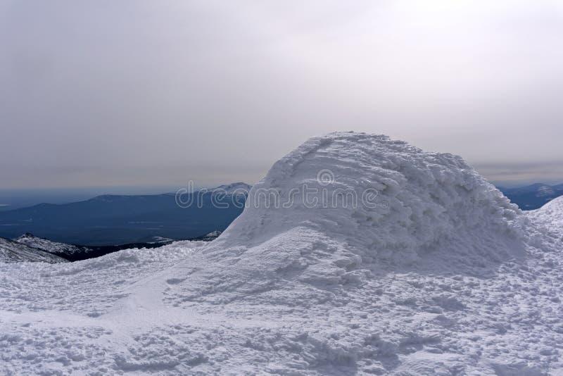 Sikt från den med is bergöverkanten till vinterdalen fotografering för bildbyråer