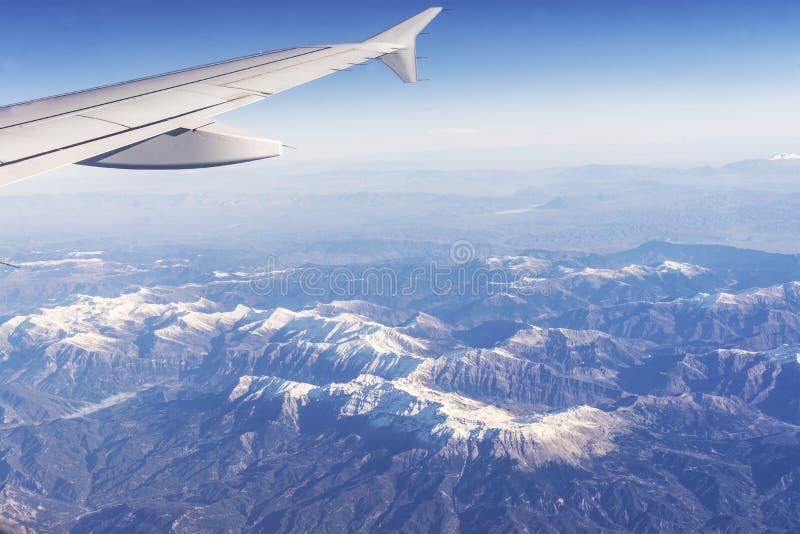 Sikt från det plana fönstret till de snöig maxima av bergen arkivfoto