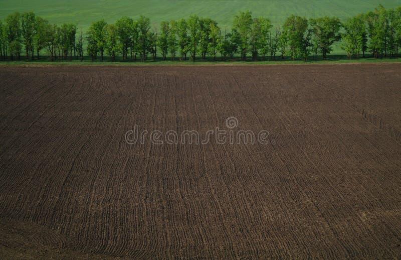Sikt från en höjd i ett plogat fält arkivbild