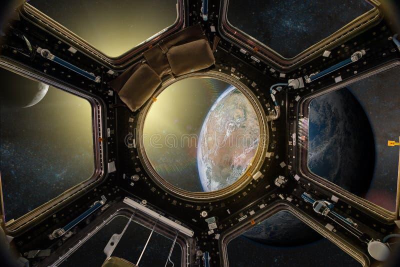 Sikt från en hyttventil av rymdstationen på jordbakgrunden royaltyfria bilder