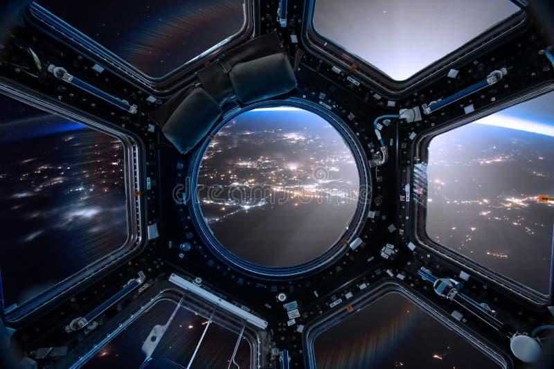 Sikt från en hyttventil av rymdstationen på jordbakgrunden arkivbild