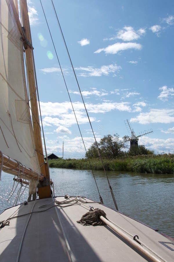 Sikt från en segelbåt nära en väderkvarn-/vindpump på den Norfolk sjödistrikt i Norfolk arkivbild