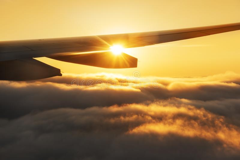 Sikt från ett flygplanfönster Oerhörda moln på solnedgången och vingen av nivån i strålarna av inställningssolen royaltyfria bilder