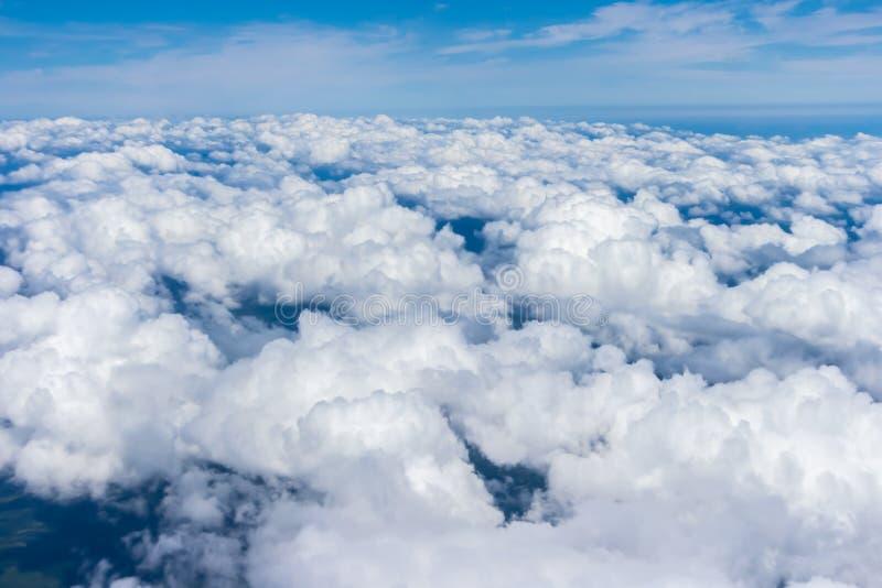 Sikt från fönstret av ett flygplan, en blå himmel och moln på Japan royaltyfri foto