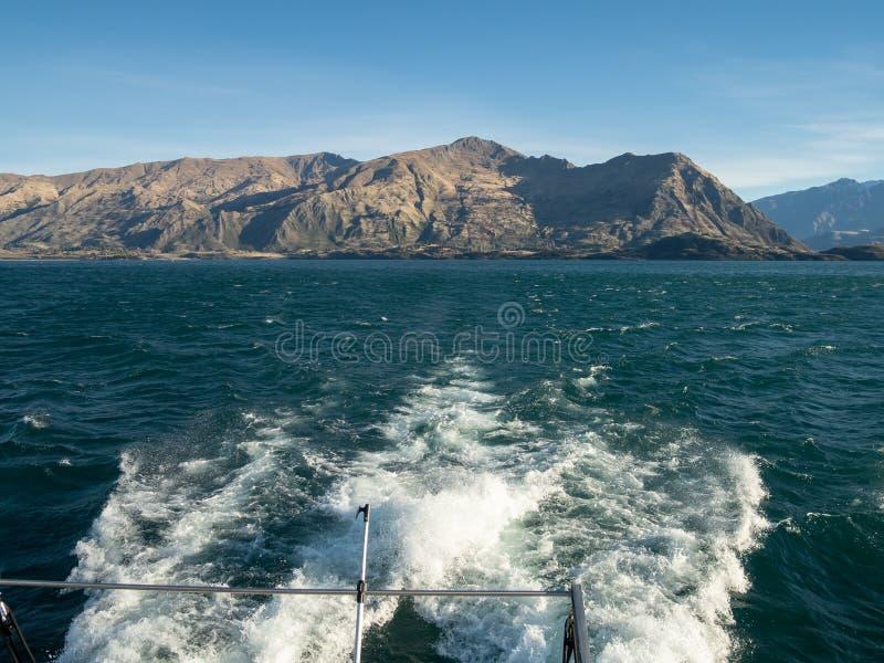 Sikt från fartyget på sjön Wanaka med berg och den skummande vaken royaltyfri fotografi