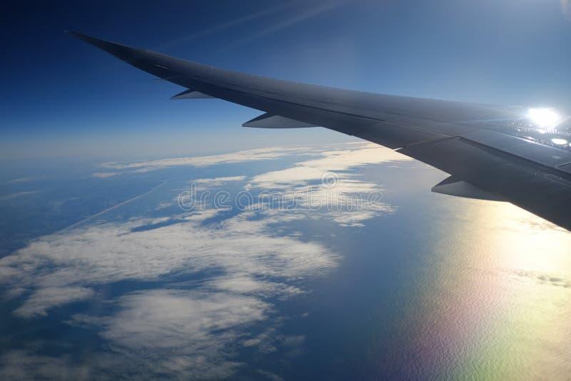 Sikt från flygplanfönster med himmel och vita moln på solnedgången royaltyfria bilder