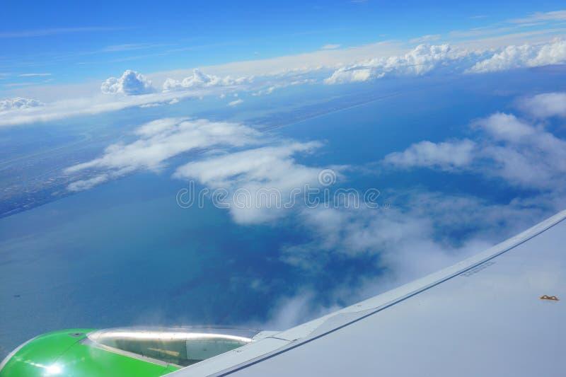 Sikt från flygplanhyttventil blå himmel, hav, kust, vinge av nivån fotografering för bildbyråer