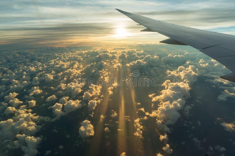 Sikt från flygplansidofönster på solnedgånghimmel och solbelysta moln royaltyfri fotografi