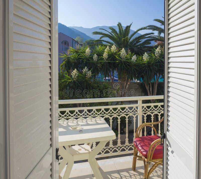 Sikt från hotellrumbalkongdörr över den vita tabellen och röd bambustol och blomningbuske och palmträd på bakgrund royaltyfri fotografi