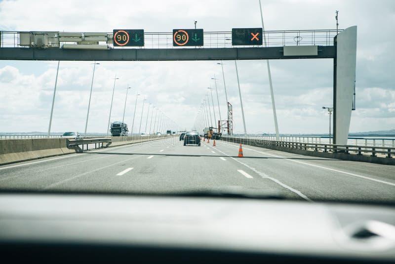Sikt från inre bilen på en asfaltväg till och med den Vasco da Gamma bron i Lissabon royaltyfri bild