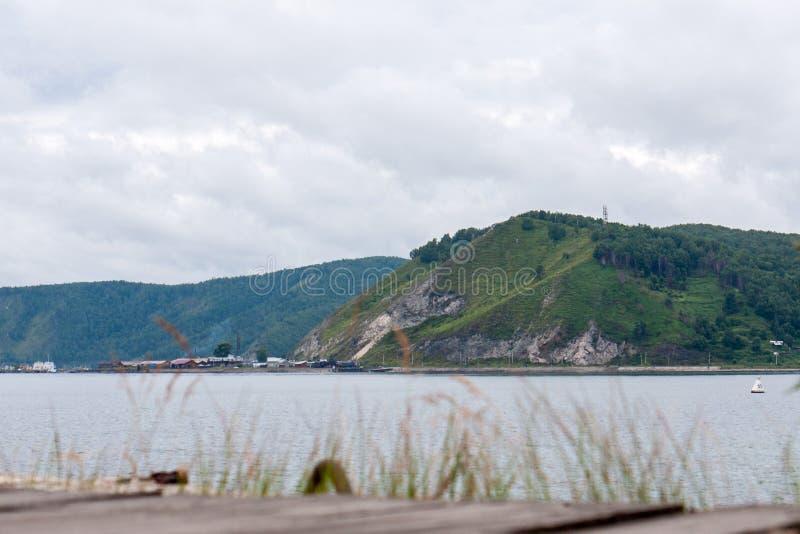 Sikt från kusten av Lake Baikal till berget och byn arkivbilder