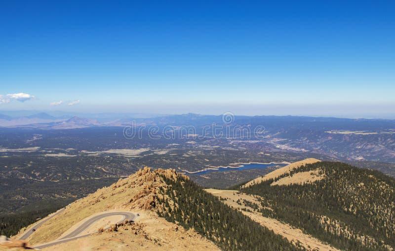 Sikt från near överkant ovanför trädlinjen av pikar maximala Colorado av hårnålkurvvägen med panorama i avstånd inklusive en sjö  fotografering för bildbyråer