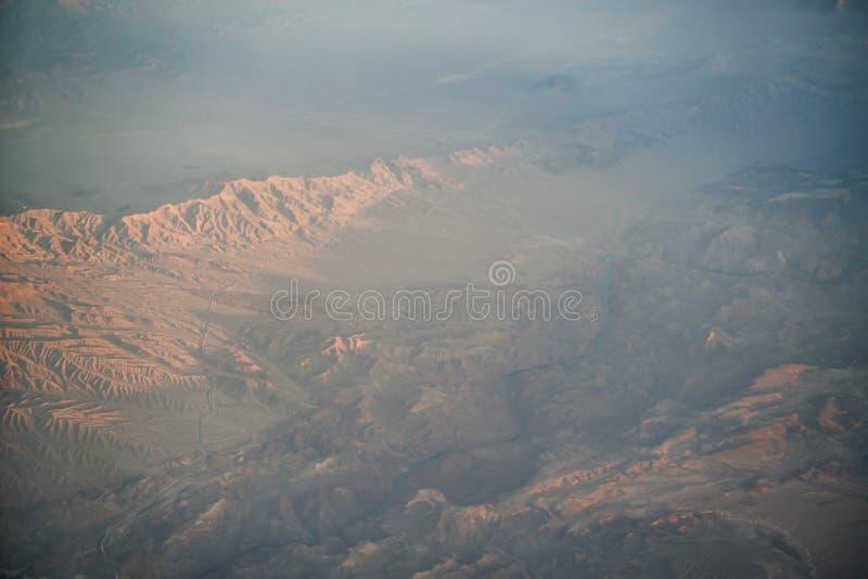 Sikt från nivån under flyg över Kalifornien berg i solnedgång royaltyfri foto