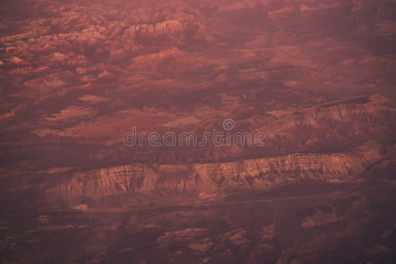 Sikt från nivån under flyg över Kalifornien berg i solnedgång arkivbild