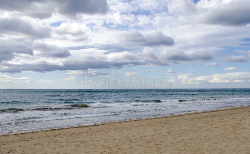 Sikt från sandstranden av det mediteranean havet med vågor och molnigt s arkivfoto