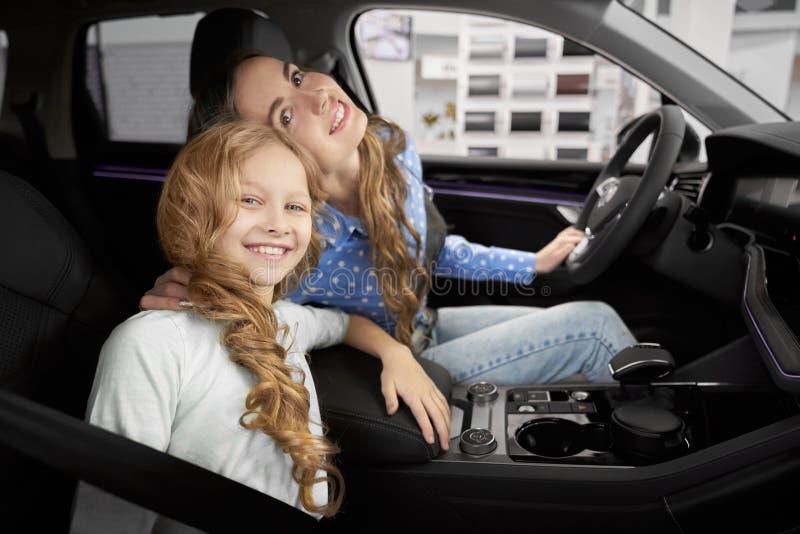 Sikt från sidan av den nätta flickan som sitter i ny bil med modern royaltyfri foto