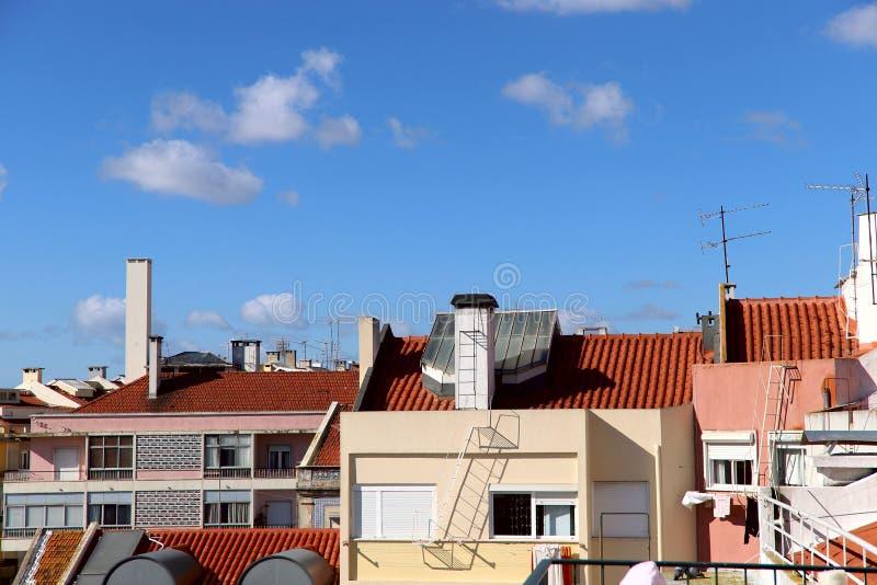 Sikt från sidan på taken av hus under de röda tegelplattorna mot den blåa himlen med vita moln royaltyfria bilder