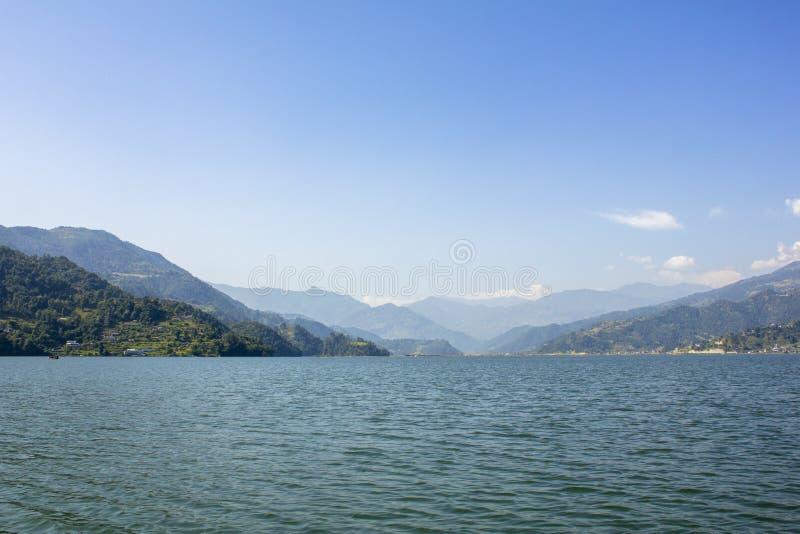 Sikt från sjön till den gröna bergdalen under den blåa himlen royaltyfri foto