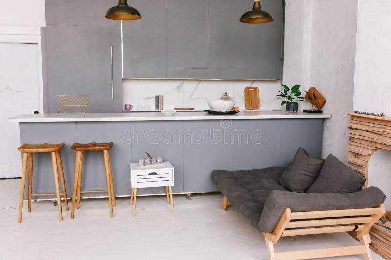 Sikt från studiokök av den nya vindlägenheten, grått möblemang royaltyfria foton