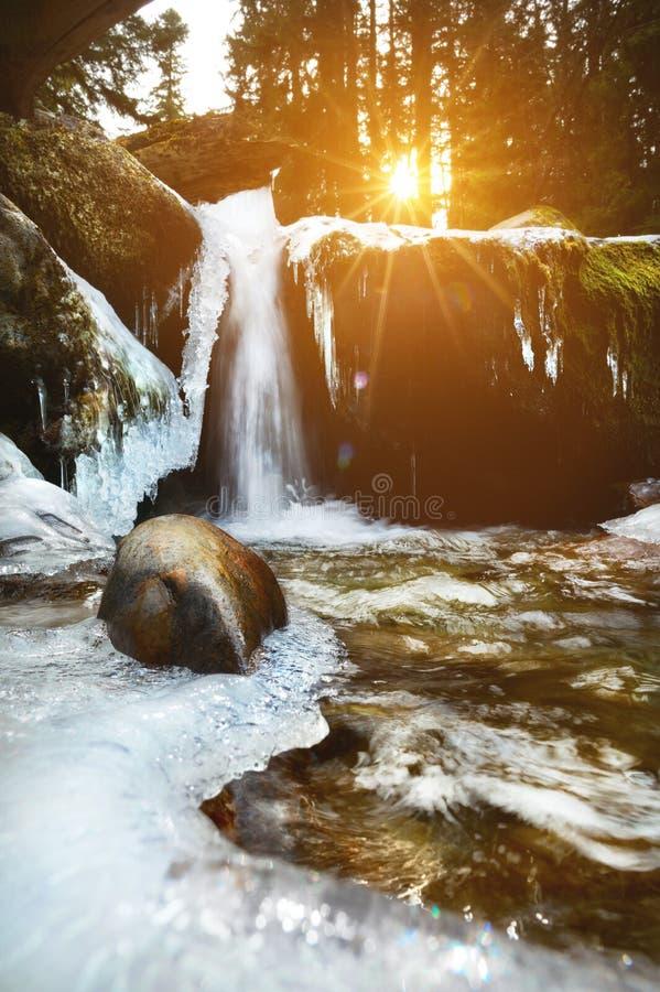 sikt från vinterlandskap Inte en stor vattenfall av en bergflod med djupfrysta banker i ljuset av inställningssolen royaltyfri fotografi
