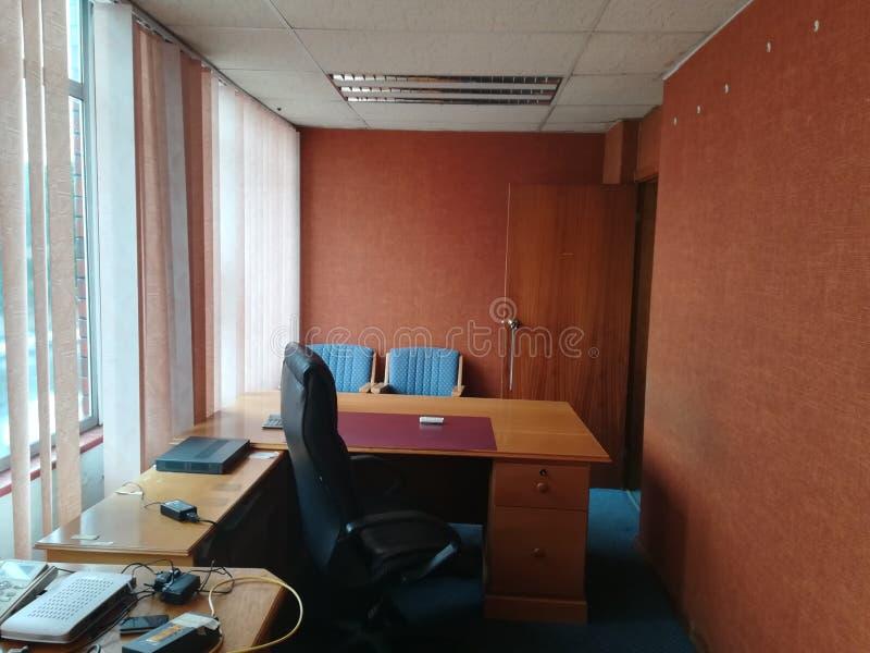 Sikt i ett kontor bakifrån ett skrivbord som ser tomma stolar fotografering för bildbyråer