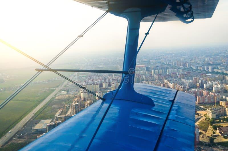 Sikt i hyttventilflygplanet av en turbopropmotorflygplanbiplan på de stadsgatorna och husen royaltyfria foton