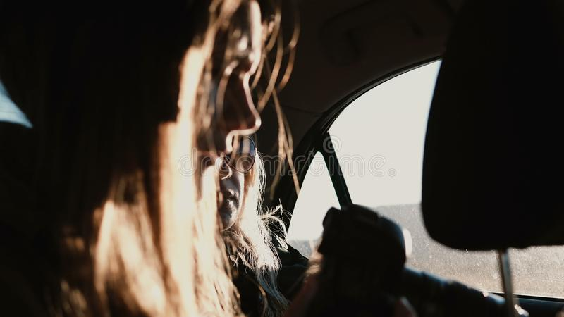 Sikt inom bilen Den turist- kvinnaresanden med bilen och tafoto av solnedgången landskap utanför fönstret royaltyfria foton