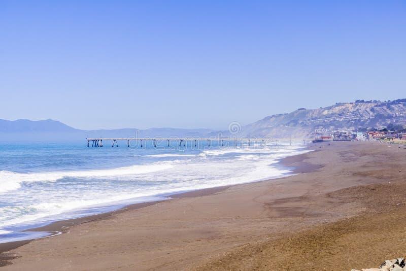 Sikt in mot den kommunala pir, Pacifica som sett från Mori Point, Marin County i bakgrunden, Kalifornien royaltyfri foto