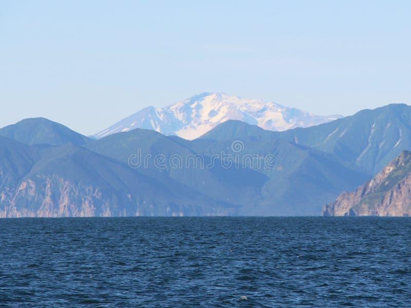 Sikt in mot den Mutnovsky vulkan från vatten på den Kamchatka halvön, Ryssland royaltyfria bilder