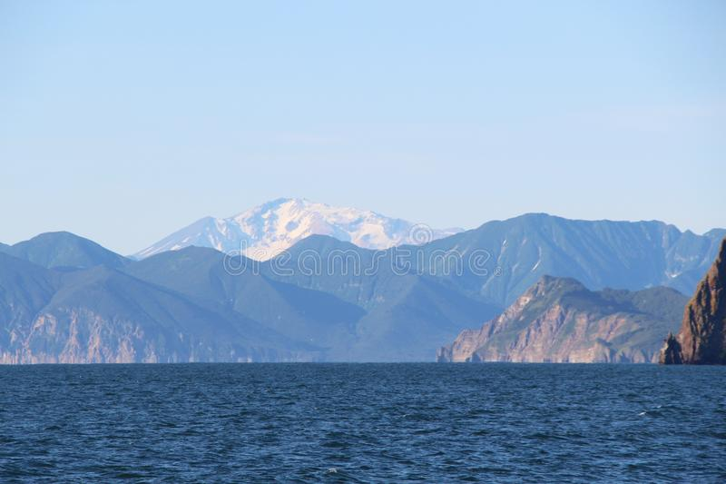 Sikt in mot den Mutnovsky vulkan från vatten på den Kamchatka halvön, Ryssland royaltyfri bild
